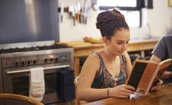 Shot of a young woman with dreadlocks reading a book in her kitchen